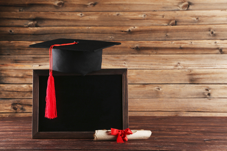 Photo pour Graduation cap with diploma and blank frame on brown wooden table - image libre de droit