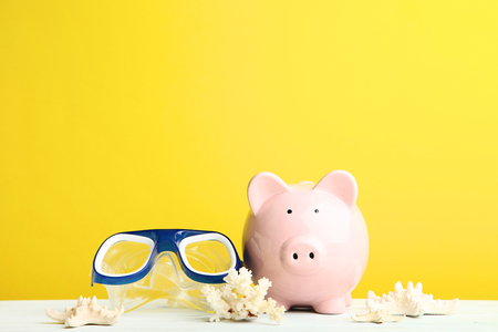 Photo pour Pink piggy bank with diving mask and snorkel on yellow background - image libre de droit