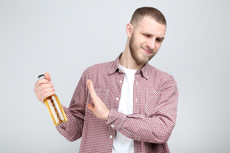 Photo pour Young man with bottle of beer on grey background - image libre de droit