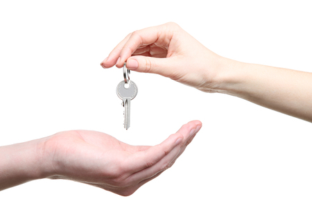 Photo pour Female's hand holding house key on white background - image libre de droit