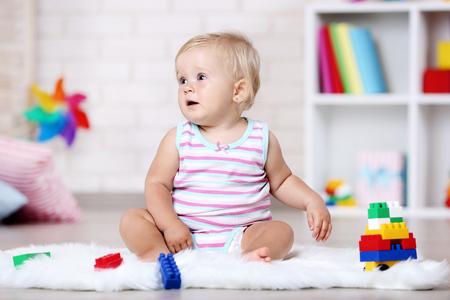 Foto für Baby girl sitting on white carpet with toys - Lizenzfreies Bild