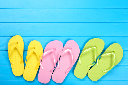 Photo for Pairs of colorful flip flops on blue wooden table - Royalty Free Image