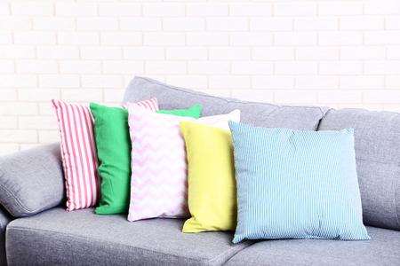 Foto de Colorful soft pillows on grey sofa - Imagen libre de derechos
