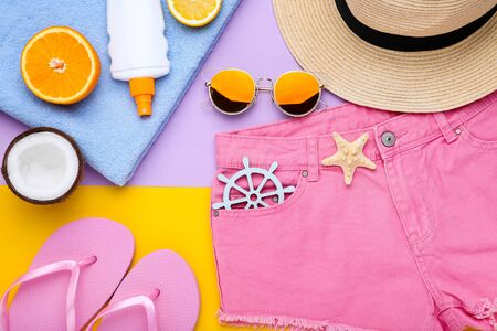 Fashion clothing with sunscreen and fruits on colorful background