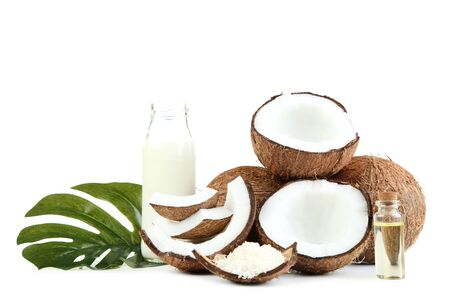 Photo for Coconut milk in bottle with oil and monstera leaf on white background - Royalty Free Image