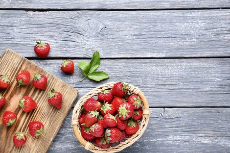 Photo pour Fresh strawberries in basket with cutting board on grey wooden table - image libre de droit