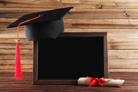 Photo for Graduation cap with diploma and blank frame on brown wooden table - Royalty Free Image