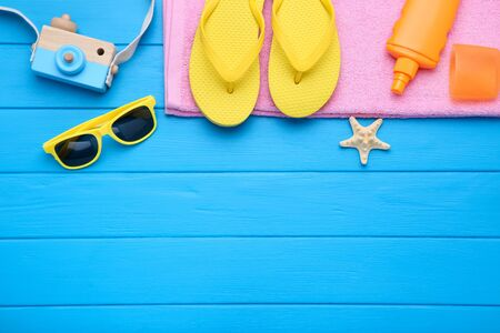Photo for Fashion clothing with starfish and sunscreen on blue wooden table - Royalty Free Image