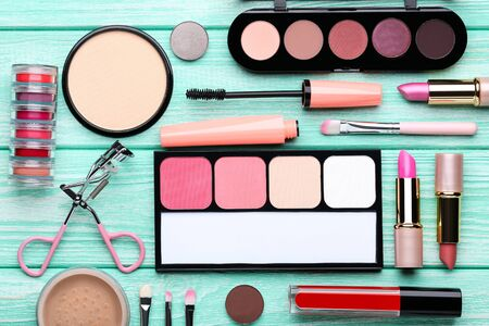 Photo for Different makeup cosmetics on mint wooden table - Royalty Free Image