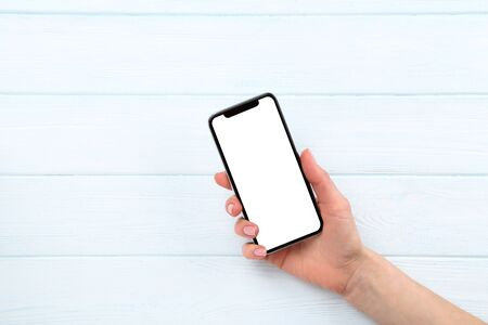 Foto de Smartphone in female hand on wooden background - Imagen libre de derechos