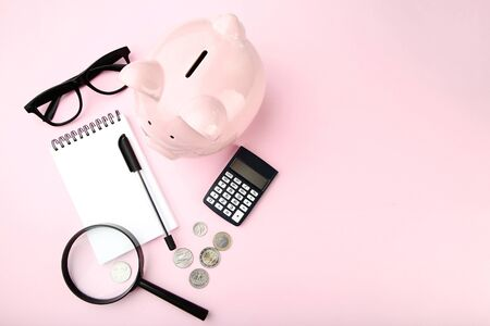 Photo for Pink piggy bank with notebook, coins and magnifying glass on pink background - Royalty Free Image
