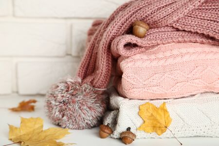 Foto per Stack of folded sweaters with scarf, acorns and autumn leafs on brick wall - Immagine Royalty Free