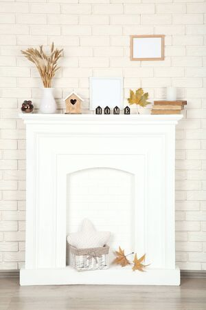 Photo pour White fireplace with photo frames, wheat ears and old books - image libre de droit