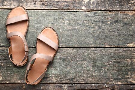Photo pour Female beige sandals on grey wooden table - image libre de droit