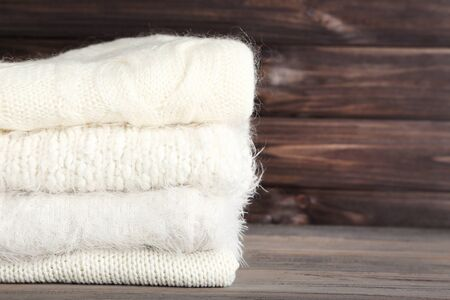 Photo pour Folded knitted sweaters on wooden background - image libre de droit