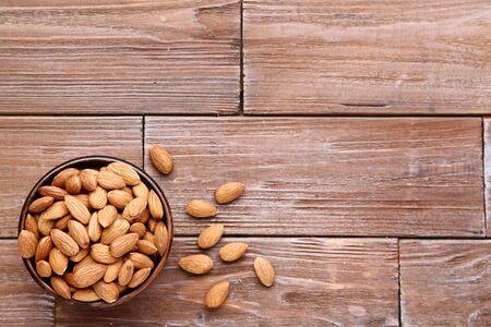 Photo pour Almonds in bowl on brown wooden table - image libre de droit