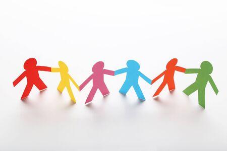 Photo pour Colorful paper chain people on white background - image libre de droit