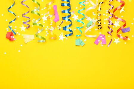 Photo for Colorful ribbons with paper stars and confetti on yellow background - Royalty Free Image