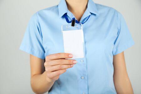 Photo pour Female hand showing blank white bagde on grey background - image libre de droit