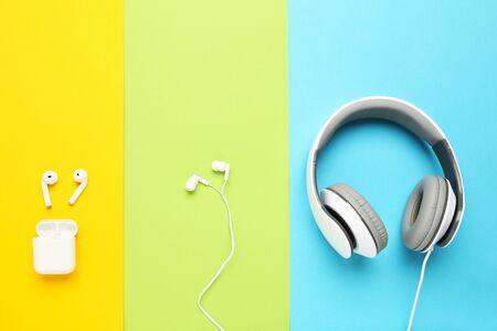 Photo pour Three different earphones on colorful paper background - image libre de droit