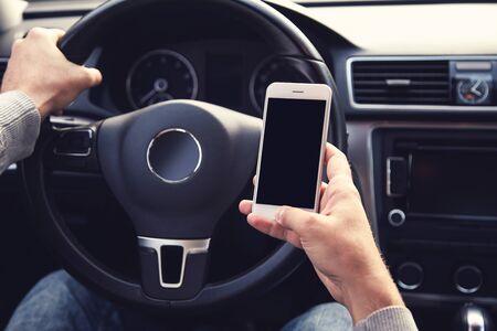 Photo pour Man using mobile phone while driving car - image libre de droit