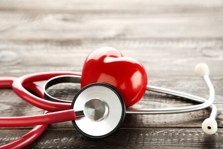 Photo pour Stethoscope with red heart on brown wooden table - image libre de droit