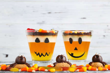 Photo for Halloween jelly in glasses with candies and cookies on wooden table - Royalty Free Image