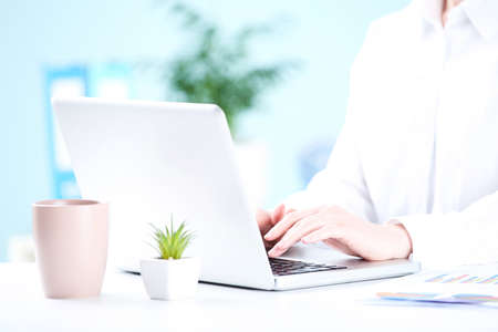 Photo pour Office worker working on a laptop with cup of drink - image libre de droit