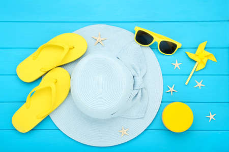 Photo pour Summer straw hat with sunglasses, flip flops, windmill and starfishes on blue wooden table - image libre de droit