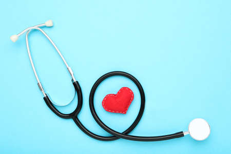 Photo pour Text Happy Doctor's Day with stethoscope and red fabric heart on blue background - image libre de droit