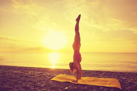 Photo pour yoga at sunset on beach. woman doing yoga - image libre de droit
