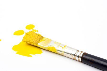 splashes of yellow paint and brush