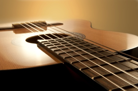 Close and low level angle capturing an acoustic guitar with warm brown background. Focus on foreground strings.
