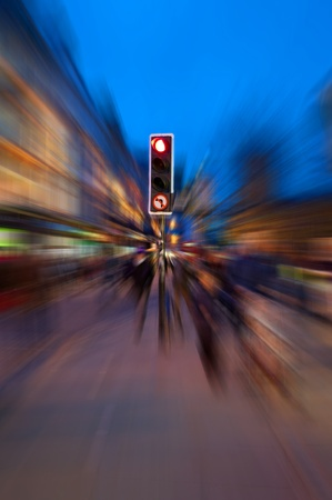 A traffic light surrounded by radial motion blur giving a chaotic concept to an evening urban street.