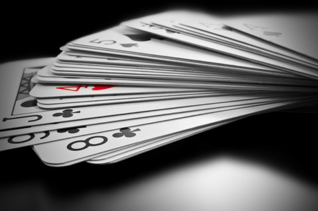 Close up on black and white deck of cards with only one card highlighted with red