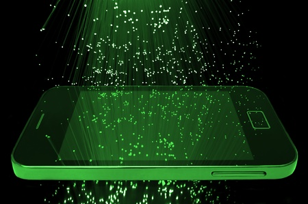 Many illuminated green fiber optic light strands cascading down against a black background and reflecting on the screen of a smart phone in the foreground