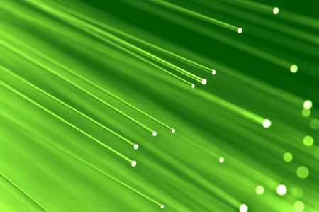 Close up on the ends of a selection of illuminated light green fiber optic light strands with green background.