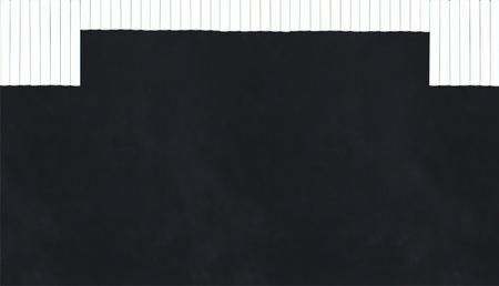 chalk sticks in a row creating a curtain on a blackboard