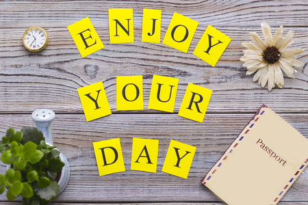 Enjoy your day printed inscription, a plant in a small pot, a watch and a passport in a cover on wooden table, top view. Creativity and motivation concept. Space for your text or product display.