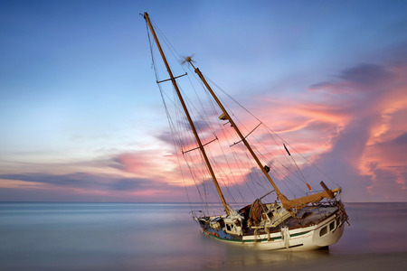 sailboat wreck in sea on the sand beach at sunset time