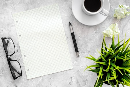 Plan for the year. Notebook, pen, glasses, cup of coffee on grey stone background top view.