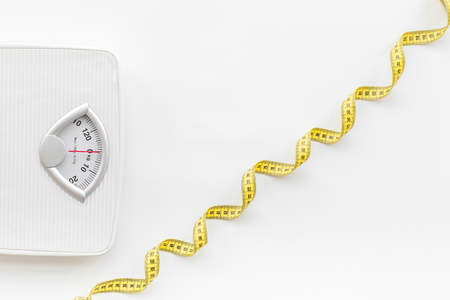 Photo pour Bathroom scale and measuring tape on white background top view. - image libre de droit