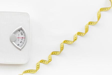 Foto de Bathroom scale and measuring tape on white background top view. - Imagen libre de derechos