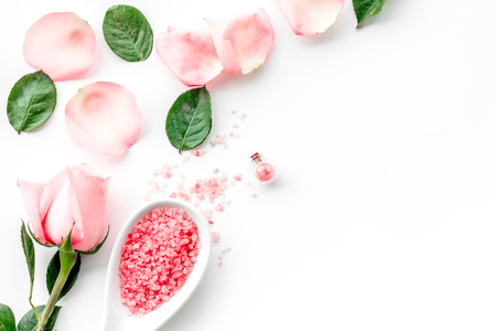 Photo for Pattern with rose oil cosmetics. Rose petals, spa salt on white background top view. - Royalty Free Image