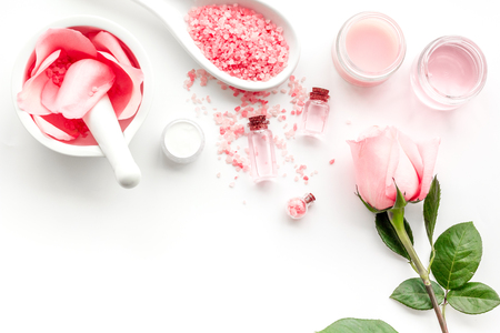 Make cosmetics with rose  oil. Mortar with rose petals and pestle on white background top view.
