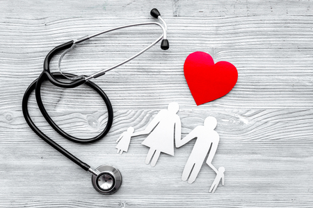 Photo pour Choose health insurance. Stethoscope, paper heart and silhouette of family on grey wooden background top view - image libre de droit