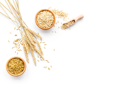 Photo for Oatmeal and oat in bowls near sprigs of wheat on white background top view. - Royalty Free Image
