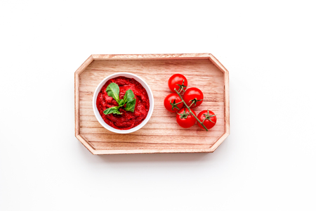 Tomato sauce in bowl with green basil near cherry tomatoes in wooden tray on white background top view copy space