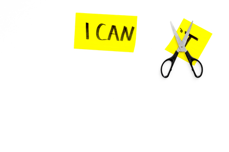 Photo pour Self confidence concept. Cutting the letter 't' of written word I cant by scissor. White background top view copy space - image libre de droit