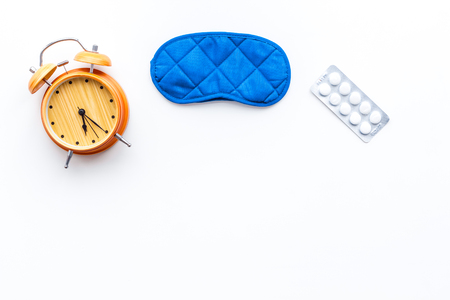 Photo pour Insomnia concept. Trying to sleep. Help yourself get to sleep. Sleeping pills near sleeping mask and alarm clock on white background top view copy space - image libre de droit